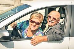 Die glücklichen älteren Paare, die zu einem Auto bereit sind, lösen aus Stockfotos