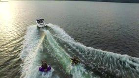 Die glücklichen aufgeregten Leute, die aufblasbaren Wasserschlauch reiten, schieben Anziehungskraft mit Motorboot, wenn sie Luftm stock video footage