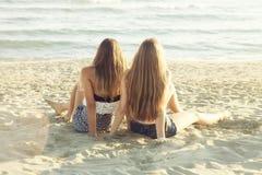 Die glücklichen blonden Jugendlichfreunde, die vor dem Meer bei Sonnenuntergang sich entspannen, unterstützen Schuss lizenzfreie stockfotografie