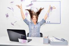 Die glücklichen braunhaarigen Würfe des Mädchens in die Luft berechnet 500 Euros Erfolgskonzept einer jungen Frau lizenzfreie stockfotografie