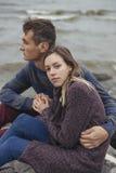 Die glücklichen durchdachten Paare, die auf einem Felsen sitzen, setzen nahe Seedem umarmen auf den Strand stockfoto