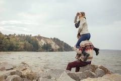 Die glücklichen durchdachten Paare, die auf einem Felsen sitzen, setzen nahe Seedem umarmen auf den Strand lizenzfreie stockbilder