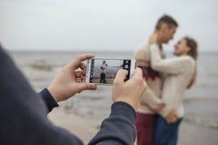 Die glücklichen durchdachten Paare, die auf einem Felsen stehen, setzen nahe Meer-huggin auf den Strand stockfotos