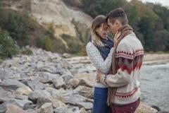 Die glücklichen durchdachten Paare, die auf einem Felsen stehen, setzen nahe Meer-huggin auf den Strand lizenzfreies stockfoto