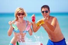 Die glücklichen Freunde, die das Kühlen halten, trinkt auf dem Strand lizenzfreies stockfoto