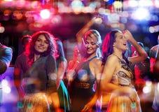 Die glücklichen Freunde, die in Verein mit Feiertagen tanzen, beleuchtet Stockbilder