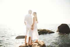 Die glücklichen gerade verheirateten jungen feiernden Hochzeitspaare und haben Spaß bei schönem Strandsonnenuntergang Stockbilder