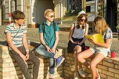 Die glücklichen 4 Jugendfreunde oder hohe Schüler haben Spaß und sprechen und lesen Telefon, Buch Freundschaft und Leutekonzept,  stockbilder