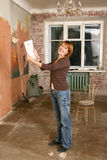 Die glücklichen jungen Frauen in der schmutzigen Wohnung Lizenzfreies Stockfoto