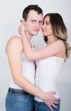 Die glücklichen jungen Paare, die einen vertrauten Moment, viel lachend genießen und bemannen streicht leicht das Haar seines Par stockfoto