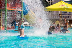 Die glücklichen Kinder, die Spaß im Wasser Parkpool mit haben, spritzt vom Wasser stockfotografie