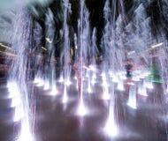 Die glücklichen Kinder, die in einem Wasserbrunnen am Abend spielen, beleuchtet lizenzfreie stockfotografie