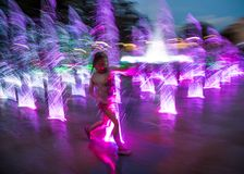 Die glücklichen Kinder, die in einem Wasserbrunnen am Abend spielen, beleuchtet stockbild