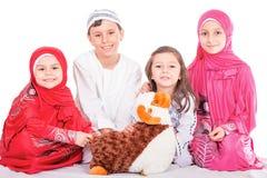 Die glücklichen kleinen moslemischen Kinder, die mit Schafen spielen, spielen - das Feiern E-I Stockfotos