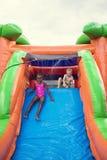 Die glücklichen lächelnden Kinder, die auf einem aufblasbaren Dia spielen, prallen Haus auf Stockbild