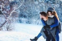 Die glücklichen liebevollen Paare, die in den Wald des verschneiten Winters, Weihnachten aufwendend gehen, machen zusammen Urlaub stockbilder