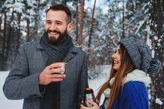 Die glücklichen liebevollen Paare, die in den Wald des verschneiten Winters, Weihnachten aufwendend gehen, machen zusammen Urlaub stockbild