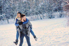 Die glücklichen liebevollen Paare, die in den Wald des verschneiten Winters, Weihnachten aufwendend gehen, machen zusammen Urlaub stockfoto