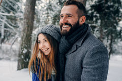 Die glücklichen liebevollen Paare, die in den Wald des verschneiten Winters, Weihnachten aufwendend gehen, machen zusammen Urlaub stockfotografie
