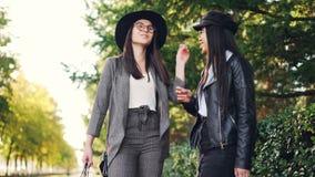 Die glücklichen Mädchen sind, lachend plaudernd und draußen stehen auf dem Bürgersteig, der helle Einkaufstaschen Tag im Mall bes stock video footage