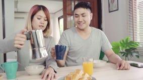 Die glücklichen süßen asiatischen Paare, die, Getreide in der Milch, Brot frühstücken und Orangensaft nach trinken, wachen morgen stock footage