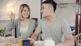 Die glücklichen süßen asiatischen Paare, die, Getreide in der Milch, Brot frühstücken und Orangensaft nach trinken, wachen morgen stock video