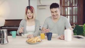 Die glücklichen süßen asiatischen Paare, die, Getreide in der Milch, Brot frühstücken und Orangensaft nach trinken, wachen morgen stock video footage