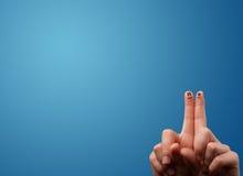 Die glücklichen smileygesichtsfinger, die leeren blauen Hintergrund betrachten, kopieren lizenzfreie stockbilder