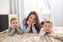 Die gl?ckliche junge Mutter, die im hellblauen Pyjama gekleidet wird, legt mit ihren zwei kleinen S?hnen, die an ihre H?nde unter lizenzfreie stockbilder