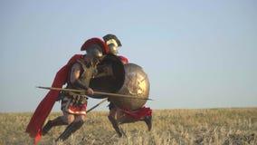 Die Gladiatorschläge, wenn man seinen Gegner mit einer Stange und ihm springt, wird durch ein Schild, Zeitlupe abgeschirmt stock video