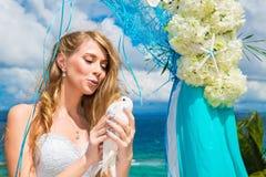 Die glückliche Braut mit weißen Tauben auf einem tropischen Strand unter Palme Stockfoto
