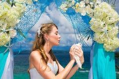 Die glückliche Braut mit weißen Tauben auf einem tropischen Strand unter Palme Stockfotografie
