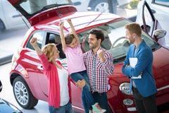 Die glückliche Familie, die gerade feiert, kaufte einen Neuwagen Lizenzfreie Stockfotografie