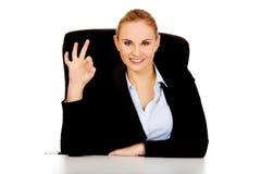 Die glückliche Geschäftsfrau, die hinter dem Schreibtisch sitzen und die Shows unterzeichnen O.K. Stockbild