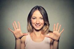 Die glückliche junge Frau, die fünfmal macht, unterzeichnen Geste mit den Händen Stockfoto