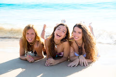 Die glücklichen drei Freundmädchen, die auf Strand liegen, versanden das Lächeln Lizenzfreie Stockbilder