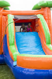 Die glücklichen lächelnden Kinder, die auf einem aufblasbaren Dia spielen, prallen Haus auf Stockfoto