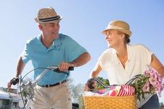 Die glücklichen älteren Paare, die für ein Fahrrad gehen, reiten in die Stadt Stockfoto