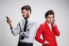 Die goldene Taste oder Erreichen für den Himmel zum Eigenheimbesitze Die zwei jungen Kollegen, die Handys auf grauem Hintergrund  Lizenzfreie Stockbilder