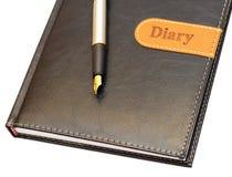 Die Goldfeder, die auf einem Tagebuch liegt Stockfotografie