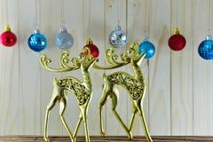 Die Goldzahlen von Rotwild und von Weihnachtsverzierungen auf hölzernem backg Lizenzfreies Stockbild