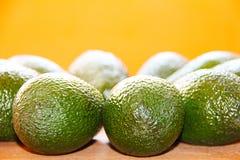 Die grüne Avocado auf einem hölzernen Brett auf einem orange Hintergrund Stockbild