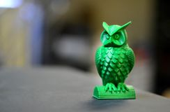 Die grüne Form in Form einer kleinen Eule hergestellt auf Dunkelheitshintergrund des Druckers 3d Stockfoto