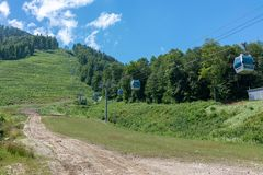 Die grüne Steigung des Berges mit den Drahtseilbahnen lizenzfreie stockfotografie