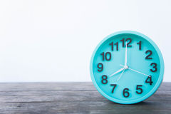 Die grüne Uhr auf einem Holztisch auf einem weißen Hintergrund Stockbilder
