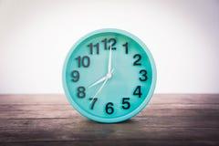 Die grüne Uhr auf einem Holztisch auf einem weißen Hintergrund Lizenzfreies Stockbild