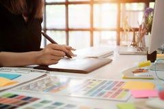 Die Grafikdesignerfrau, die an kreativem Büro mit arbeitet, stellen GR her Stock Abbildung
