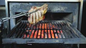 Die Grillpartei, die auf dem offenen Feuer kocht Schweinefleischsteak sich entspannen oder das Rindfleisch dreht große Metallhalt stock video