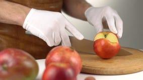 Die Großaufnahme des Mannes, der sorgfältig den roten Apfel schneidet stock video