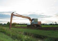 Die große Löffelbaggerbaggermaschine auf dem grünen Reisgebiet Lizenzfreie Stockfotos